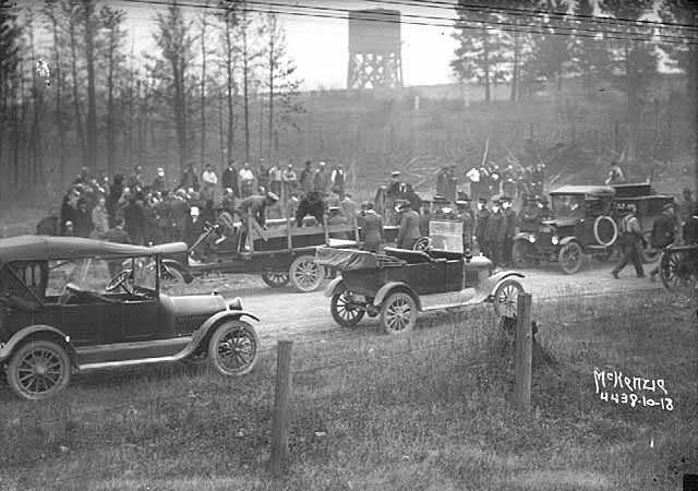 Black and white photograph of relief workers unloading coffins from Motor Corps vehicles after the fires of 1918.