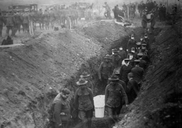 Black and white photograph of Minnesota Home Guardsmen burying dead of the Fires of 1918.