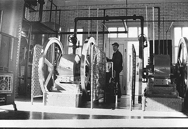 Black and white photograph of Assistant keeper Tom Hassing standing next to diesel air compressors at Split Rock Lighthouse c.1945.