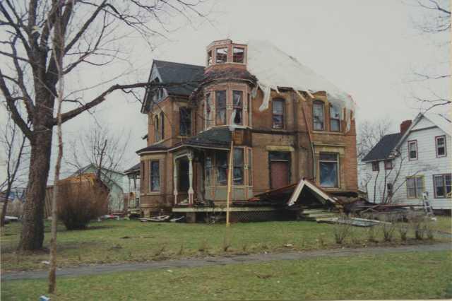 Photograph of badly damaged house.