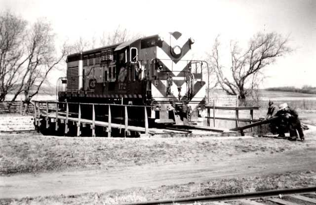 Black and white photograph of en turning a diesel locomotive on the Chicago, St. Paul, Minneapolis & Omaha turntable, ca. 1950s or 1960s.