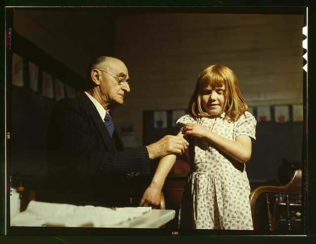 Dr. Schreiber of San Augustine giving a typhoid innoculation at a rural school, San Augustine County, Texas
