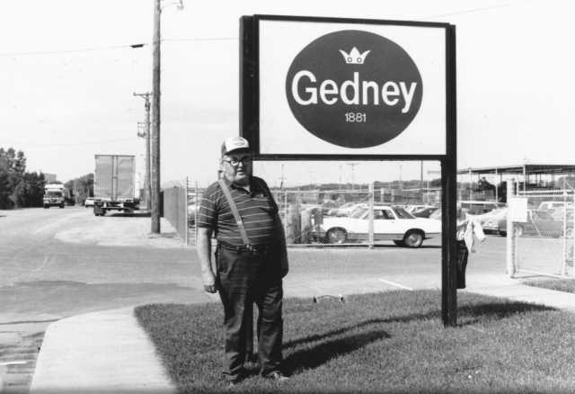 Black and white photograph of a man standing to the left of the Gedney sign, outside the Chaska factory,  c.1980s.