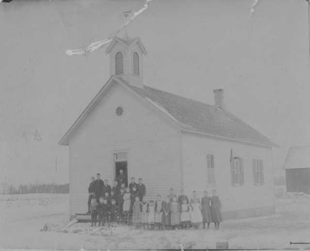 Photograph of Mayer public school (District #73) c.1895. Teacher Thomas Burns stands with his students outside the one-room schoolhouse. Photograph Collection, Carver County Historical Society, Waconia.