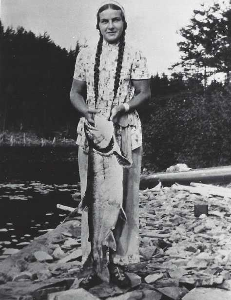 Black and white photograph of Dorothy Molter holding a lake trout, ca. 1940s.
