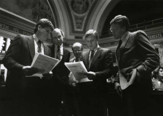 Black and white photograph of Ron Dicklich, William Luther, Allan Spear, Roger Moe, and Duane Benson reading a bill on the floor of the Minnesota Senate, 1988.