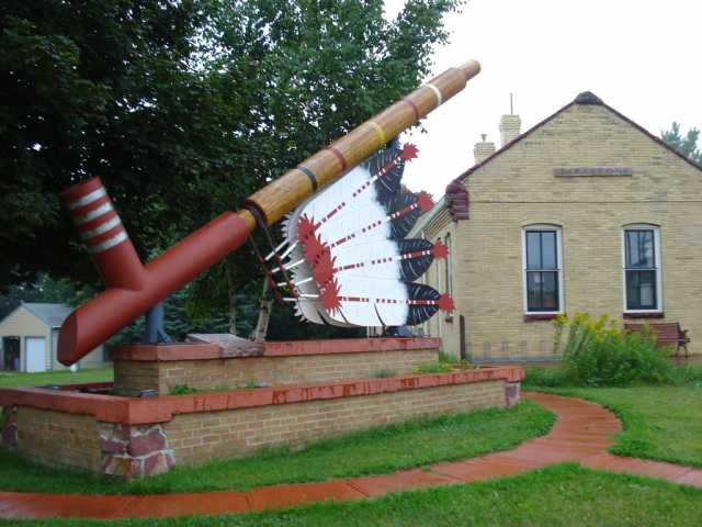 Color image of the world's largest peace pipe, installed next to the Rock Island Depot in Pipestone. Photographed by Flickr user Josh Mattson, August 15, 2009.