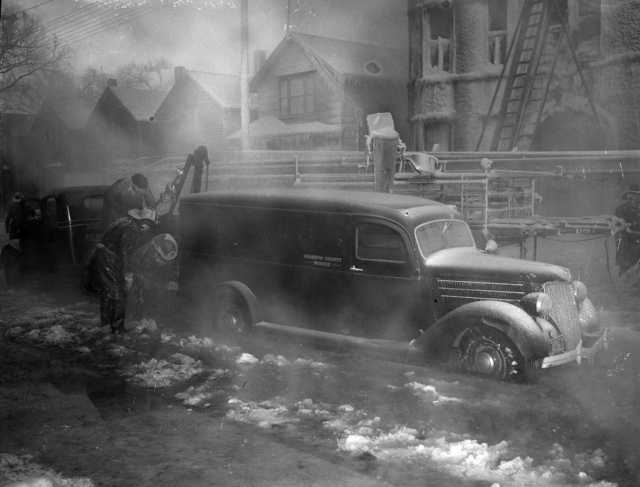 Photograph of Minneapolis firefighters trying to move a Hennepin County Morgue truck after being iced in during a January 3, 1940 fire at the Marlborough Apartment Hotel