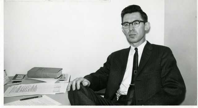 Black-and-white photograph of Professor Roy W. Meyer at his Mankato State College desk in the early 1960s.