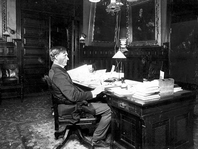 Governor John Lind seated in his office in the State Capitol
