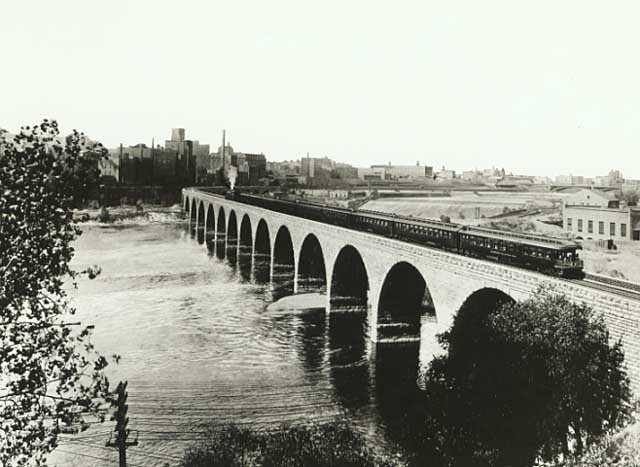 Train on the Stone Arch Bridge crossing the Mississippi River, Minneapolis; mill