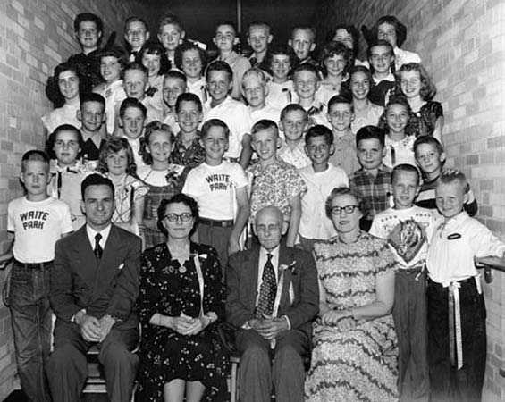 Black and white photograph of Edward F. Waite posed with students at Waite Park School, c.1955.