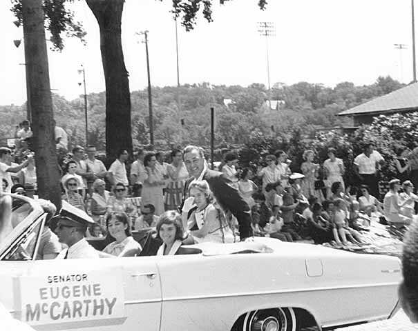 Black and white photograph of Eugene McCarthy in a parade, with daughters Ellen, Mary, and Margaret McCarthy, c.1964.