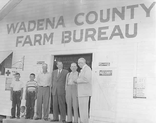 Photograph of Val Bjornson in front of Wadena County Farm Bureau Building with Joe Langer, Fred Miller and others, c. 1954.