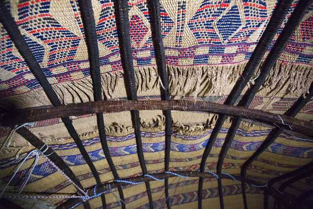 Photograph of the interior roof of an aqal, a traditional Somali home held together by ropes and thick branches and covered with kabad (hand-woven mats)