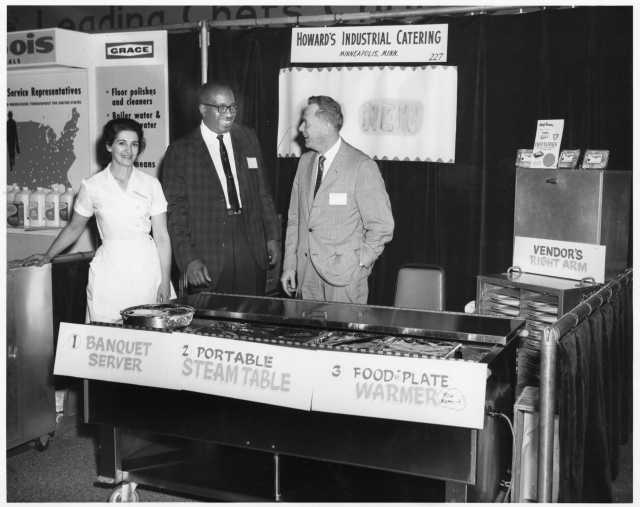 Restaurant trade-show booth for Howard's Industrial Catering displaying patented heated food carriers, ca. 1960s. Photo by H. M. Schwang Photo Company. Oscar C. Howard papers, 1945–1990, Cafeteria and Industrial Catering Business, Manuscripts Collection, Minnesota Historical Society.