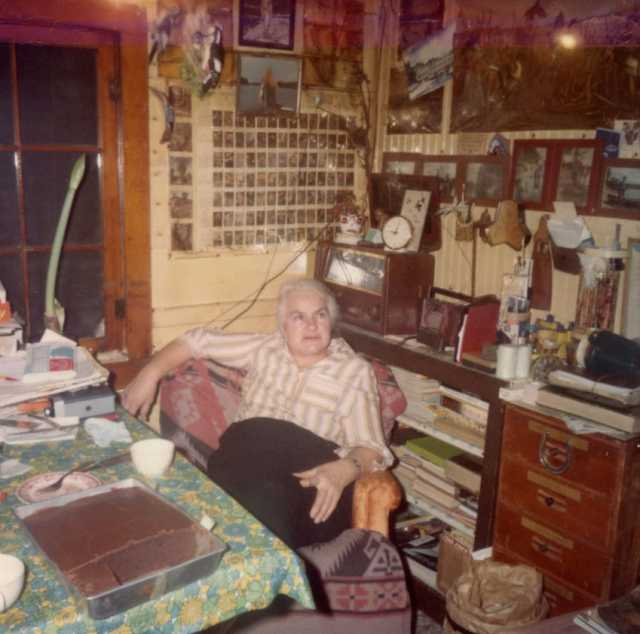 Color image of Dorothy Molter sitting at the kitchen table of the Point Cabin, Isle of Pines, Knife Lake, Boundary Waters Canoe Area, ca. 1970s.