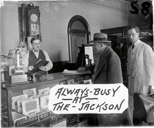Image from a glass plate negative showing the front desk of the Jackson Hotel, ca. 1926. Cigars for sale are visible in the case, and a timetable for the Anoka Electric Line is fixed to the back of the cash register. Art Anderson is one of the men in the photograph. This image was used as an advertisement at Green's Theater, located on Main Street in Anoka a few blocks from the hotel. Photographer unknown. Used with the permission of the Anoka County