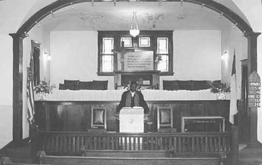 Black and white photograph of Rev. Alphonse Reff standing in the pulpit at St. Mark's African Methodist Episcopal Church, Duluth, July 8, 1975.