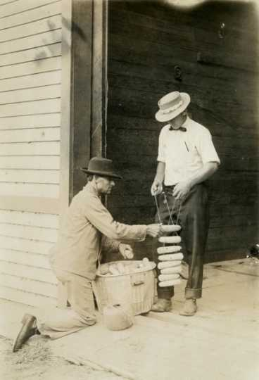 Black and white photograph of two individuals tying up ears of corn on a rack for drying, c.1910