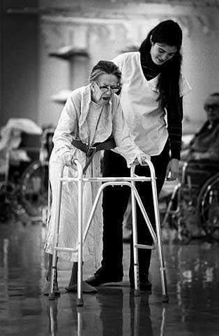 Therapist assists elderly stroke victim with a walker, Abbott-Northwestern Hospital, Sister Kenny Pavilion.