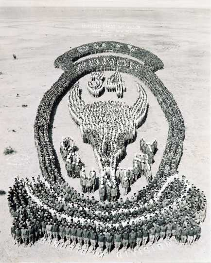 "Black and white photograph of Thirty-fourth soldiers at Camp Cody, New Mexico, form an ""animated"" image of their shoulder insignia, just prior to their departure from camp, August 18, 1918."