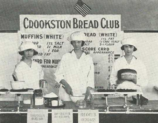Black and white photograph of three girls in the Crookston Bread Club display baked goods and the recipes used to make them, 1920.