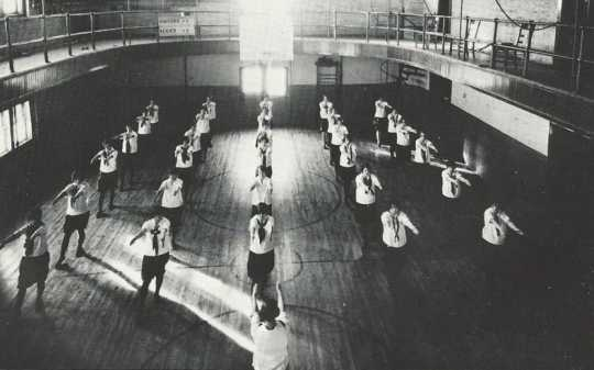 Black and white photograph of girls in uniform performing calisthenics during a physical education class on the second floor of Kiehle Hall, 1927.