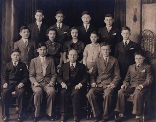 Black and white photograph of young men and women of the 1935 graduating class of the St. Paul Talmud Torah. Max Gordon, the director of the Talmud Torah, is seated at the center of the front row.