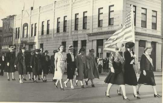 Black and white photograph of Members of Crookston's BPW club walking with the American flag down Main Street in a parade, ca. 1940s.