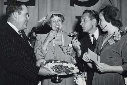 Black and white photograph of Philip Pillsbury, Eleanor Roosevelt, and Art Linkletter sampling Theodora Smafield's winning recipe, 1949.