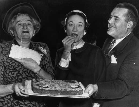 Black and white photograph of the Duchess of Windsor, the former Wallis Simpson, and Philip Pillsbury sample the grand prize winning orange kiss-me-cake cake, 1951.