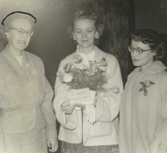 Black and white photograph of Doris Matzke being presented with a bouquet at a Crookston BPW club breakfast, September 22, 1957.