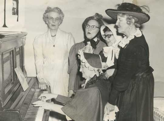 Black and white photograph of BPW members in historic costumes singing around a piano, 1958. Pictured (left to right) are Louise Rasmussen, Clara Berg, Ruth Rohrer (piano player), an unknown woman, and Maybelle Anderson.