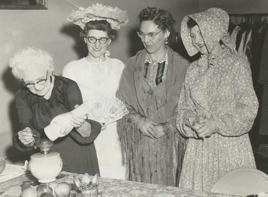 Black and white photograph of Mary Walker, a BPW charter member, lighting a kerosene lamp, 1958. With her are (left to right) Mary Walker, Mae Rohrer, Elizabeth Marsh, and Sylvia Johnson, all wearing historic costumes.