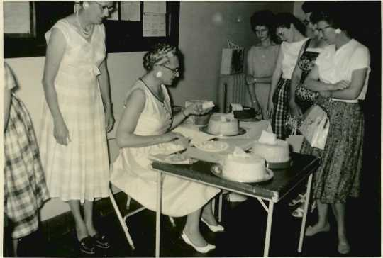 Black and white photograph of a Farm Bureau cake contest, 1960, with Mrs. Milford Peterson (seated) as judge.