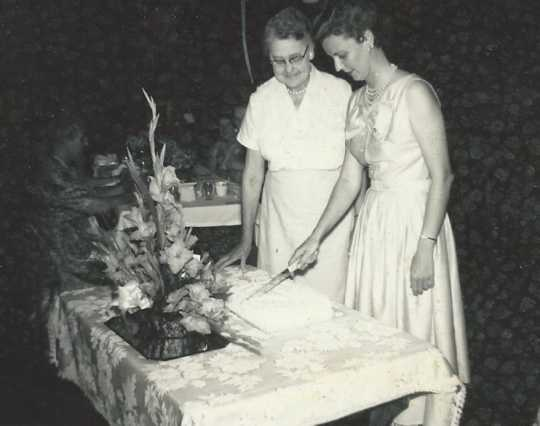 Black and white photograph of BPWC president Mary Louise Jorgenson (right) cuts cake for Ida Twedten (center), the first BPWC president, at a birthday party held for Twedten, 1966.