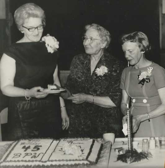 Black and white photograph of BPWC president Marian Olson, Mae Rideout, and June Shaver at a party celebrating the Crookston BPWC's forty-fifth anniversary.