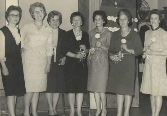 Black and white photograph of Mrs. Matzke, Miss Olson, and Miss Nelson present yellow carnations to initiates Luverne Sorenson, Deborah Hanson, Eloise Espe, and Clara Kelly at an initiation meeting for new BPWC members, 1966.