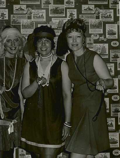 Black and white photograph of BPW members in 1920s flapper dresses at a holiday party, 1975.