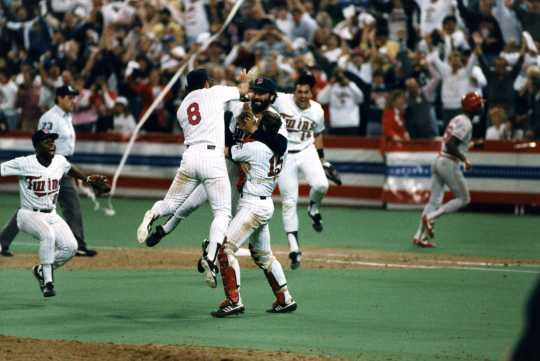 Twins relief pitcher Jeff Reardon is mobbed by catcher Tim Laudner and third baseman Gary Gaetti after the final out in the deciding Game Seven.