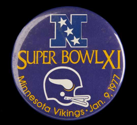 Color image of a plastic pin-back button commemorating the participation of the Minnesota Vikings in Super Bowl XI, played against the Oakland Raiders in Pasadena, California, 1977. The Raiders defeated the Vikings 32–14.