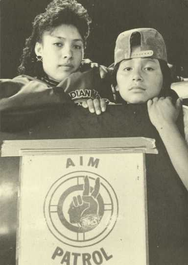 Postcard with photograph of AIM Patrol poster, 1991.
