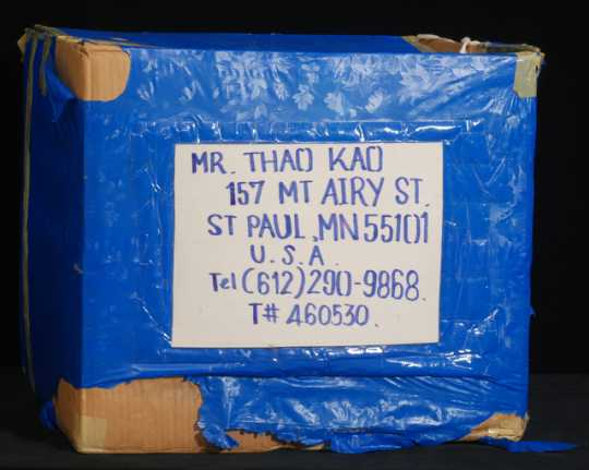Color image of a corrugated cardboard box used as a packing carton by Blia Cha Thao and family—Hmong refugees who moved from Thailand to Minnesota in 1993.