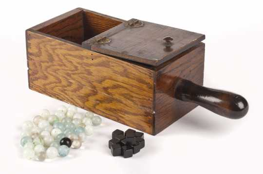 Color image of a wooden ballot box with hinged lid containing forty-two marbles and twelve black plastic cubes. Used by the Minnesota Grange.