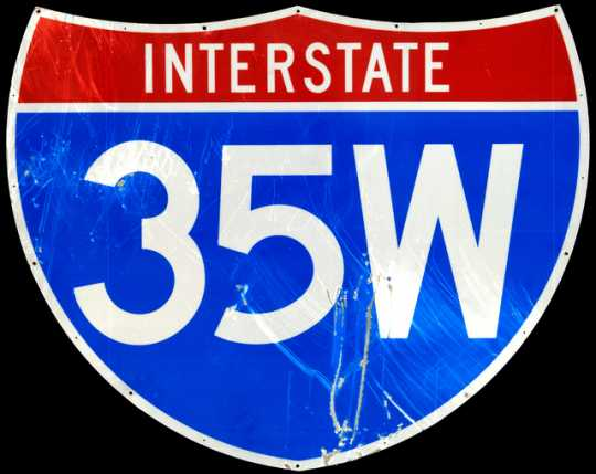Highway identification sign for Interstate 35W. The sign stood on Bridge 9340, which carried I-35W over the Mississippi River in Minneapolis. The sign stood on the bridge at the time of its collapse on August 1, 2007. Its surface is heavily scratched, and this damage may be a direct result of the collapse.