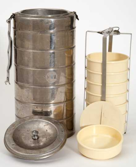 Color image of an insulated canister used to keep food warm in airline meal service. The canister, which contains eight plastic bowls, was used by Northwest Airlines, c.1950s.