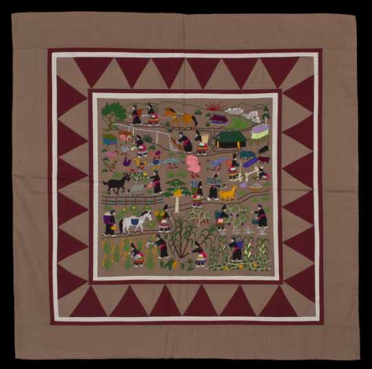 Color image of a Hmong story cloth (paj ndau) showing a traditional Laotian village scene. Made in Ban Vinai, Thailand, c.1989.