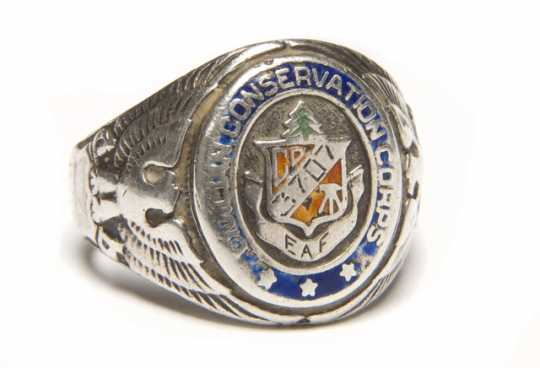 """Color image of a Sterling silver Civilian Conservation Corps ring with CCC logo flanked by an eagle and shield on opposing ends. Logo is engraved with """"3707/ and """"EAF"""". Worn by Fred Fretheim of Company 3707, Two Harbors, MN, ca. 1936–1937."""