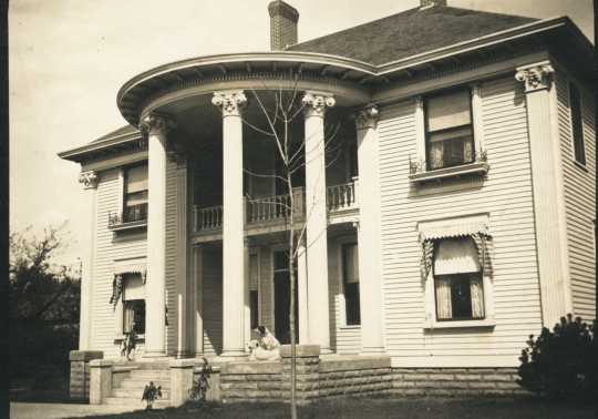 Colonial Hall (1900 3rd Avenue South, Anoka), date unknown. This was the home of Dr. Alanson Aldrich and Dr. Flora Aldrich. Alanson was an avid hunter and kept several hunting dogs in a kennel behind the house, two of which can be seen on the porch in this photograph. Photographer and date unknown. This photograph was found in the 1960s in the home of Era M. Smith, a friend of Dr. Flora Aldrich. Used with the permission of the Anoka County Historical Society.